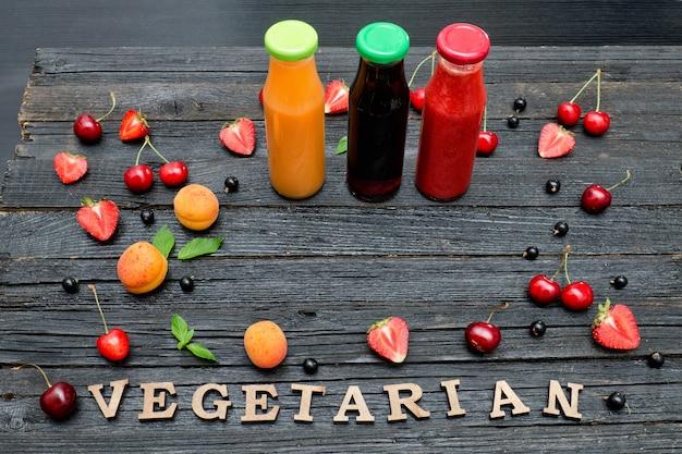 Tres botellas con jugo, fruta e inscripción vegetariano sobre fondo de madera negra. concepto de comida
