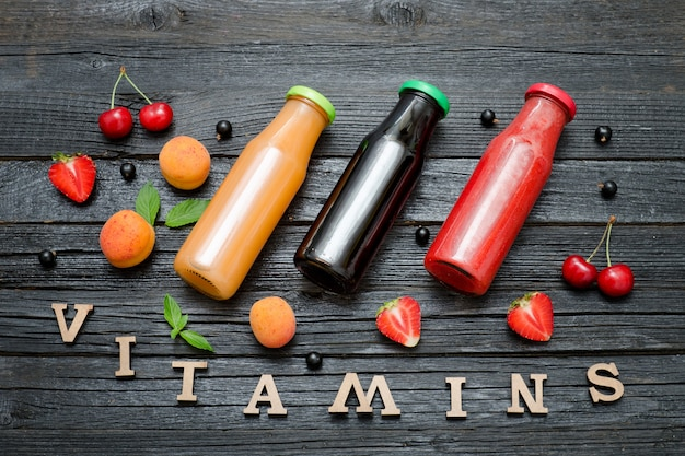 Tres botellas de jugo, fruta e inscripción vitaminas. fondo de madera