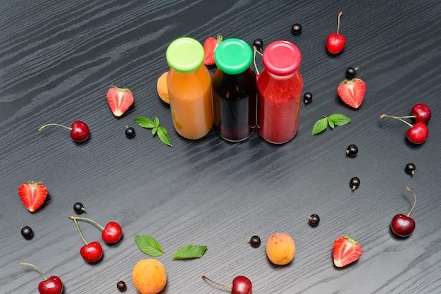 Tres botellas de jugo y frutas. mesa de madera negra. copia espacio