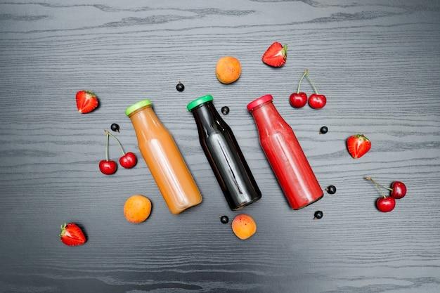 Tres botellas de jugo y frutas. negro de madera. concepto de comida