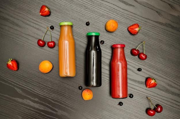 Tres botellas con jugo, frutas sobre un fondo negro de madera, concepto de comida