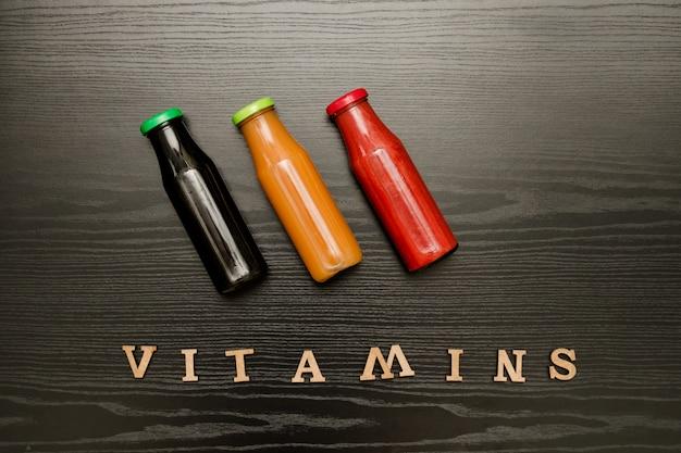 Tres botellas con jugo y vitaminas de inscripción sobre un fondo negro de madera, concepto de comida