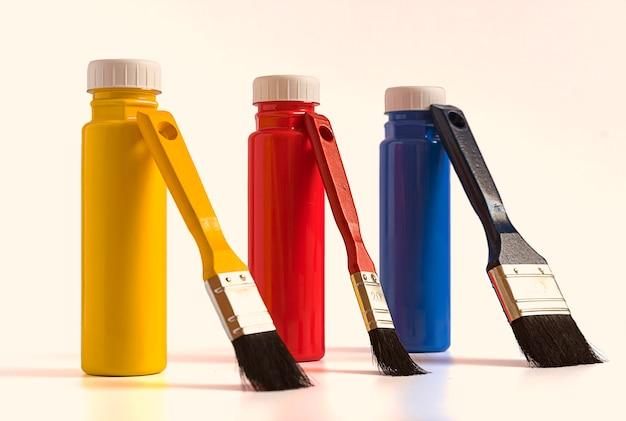 Tres botellas de pinturas acrílicas de color primario con pinceles