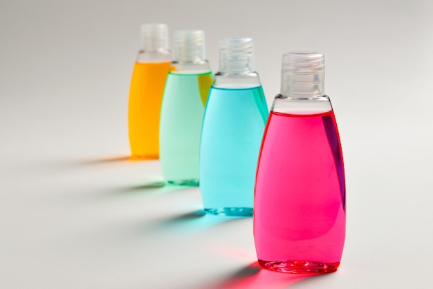 Tres botellas de plástico con jabón líquido amarillo, verde y rojo.
