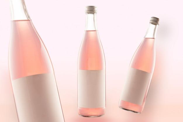 Tres botellas rosas de maquetas de bebidas de cola, vino o cerveza. etiquetas blancas vacías