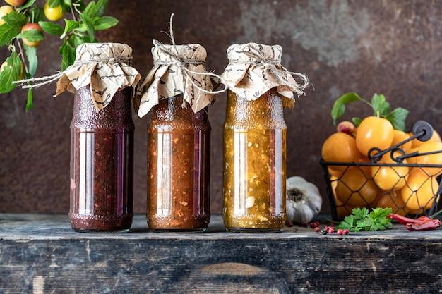 Tres botellas de vidrio de salsa tkemali georgiana variada con ingredientes sobre la mesa de madera rústica