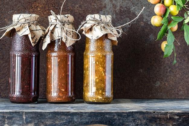 Tres botellas de vidrio de salsa tkemali georgiana variada con ingredientes sobre la mesa de madera rústica.