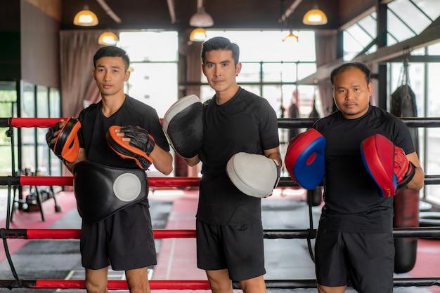 Tres boxeadores asiáticos se posan y sonríen mientras se recuestan sobre cuerdas rojas negras en el ring de boxeo y descansan después de un duro entrenamiento en el gimnasio loft negro.
