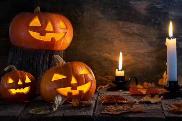 Tres calabazas de halloween cabeza jack o linterna en mesa de madera.