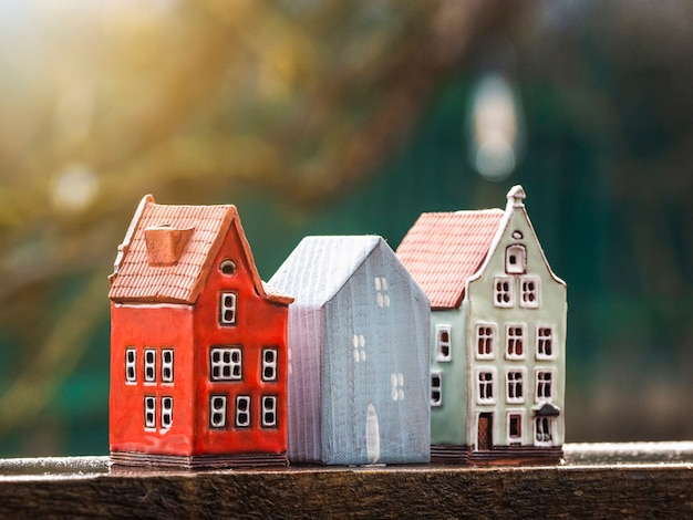 Tres casas de juguete en una soleada naturaleza borrosa. inmobiliaria, construcción, concepto de vivienda de alquiler.