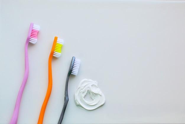 Tres cepillos de dientes sobre un fondo blanco y pasta de dientes blanca