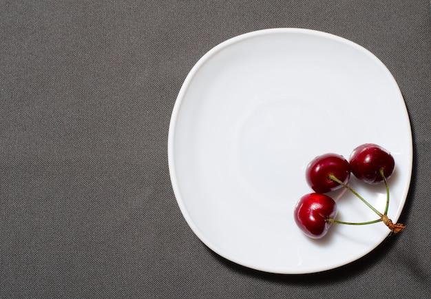 Tres cerezas en el borde de un plato vacío en la textura gris, copyspace, vista superior