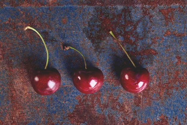 Tres cerezas maduras en la mesa vieja