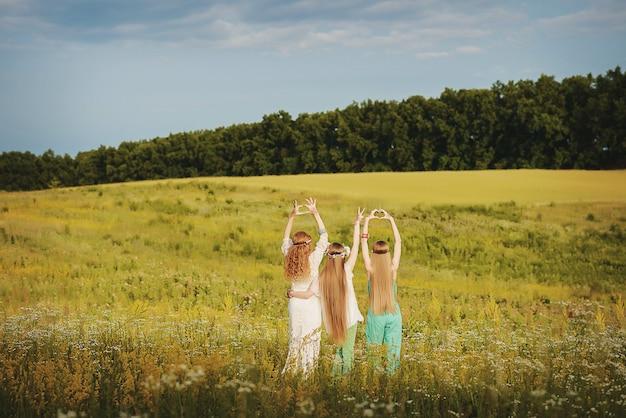 Tres chicas con coronas de flores mehendi en sus manos al estilo de boho en el campo en un día soleado de verano.