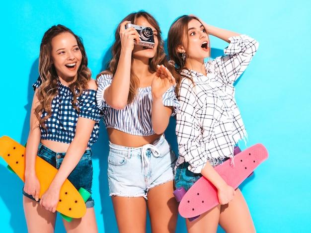 Tres chicas guapas con estilo hermosas sonrientes con patinetas coloridas centavo mujeres en ropa de camisa a cuadros de verano posando. modelos tomando fotos con la cámara de fotos retro