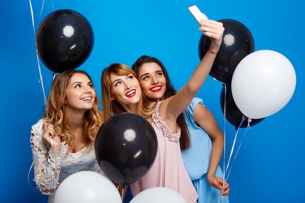 Tres chicas guapas haciendo selfie en fiesta sobre pared azul