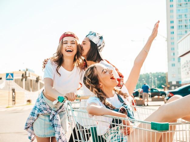 Tres chicas guapas jóvenes divirtiéndose en el carrito de compras