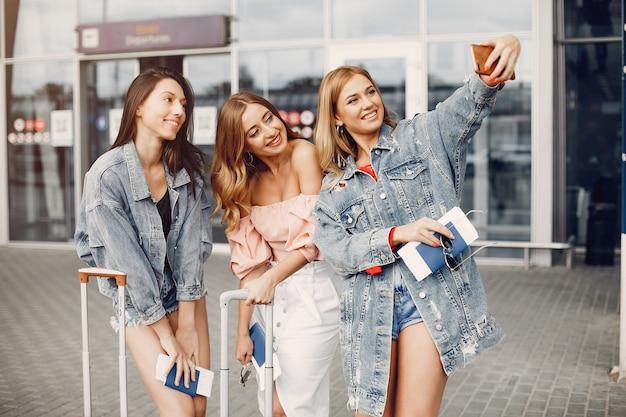 Tres chicas guapas de pie junto al aeropuerto