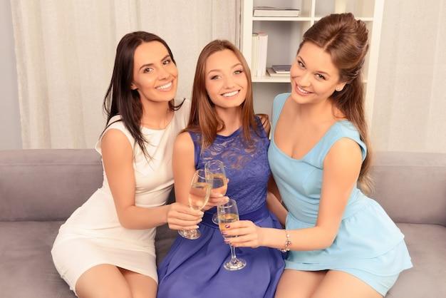 Tres chicas guapas sentadas en el sofá y tintinear con copas de vino