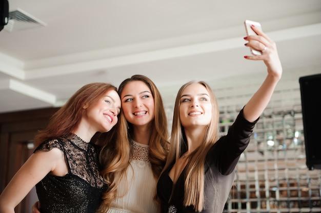Tres chicas jóvenes están haciendo una foto selfie en un restaurante.