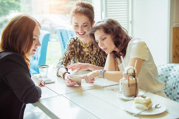 Tres chicas lindas viendo algo divertido en el teléfono inteligente en el café. señora bonita morena sosteniendo el teléfono celular en sus manos