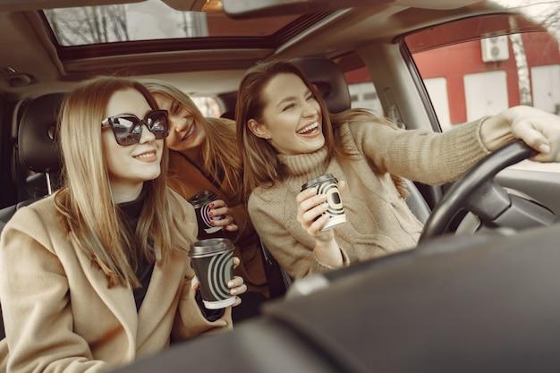 Tres chicas sentadas dentro del auto y tomando un café