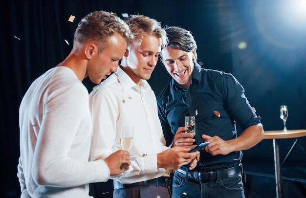 Tres chicos con ropa de fiesta conversan y miran el teléfono.