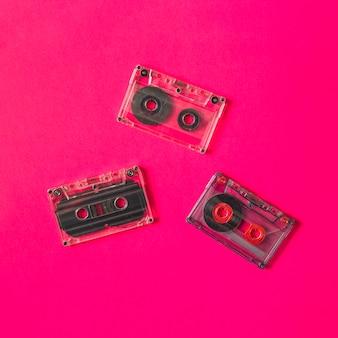 Tres cinta de cassette transparente sobre fondo rosa
