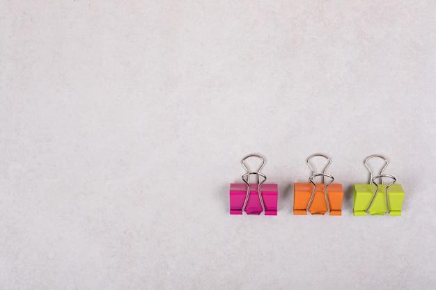 Tres clips de papel de colores sobre fondo blanco.