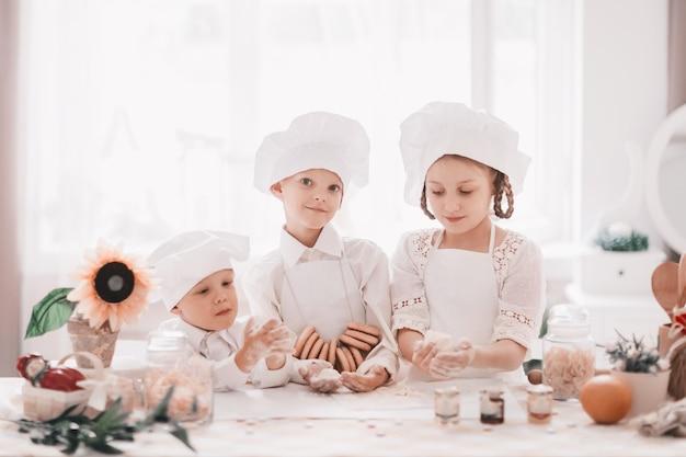 Tres cocineros de bebé feliz de pie cerca de la mesa de la cocina