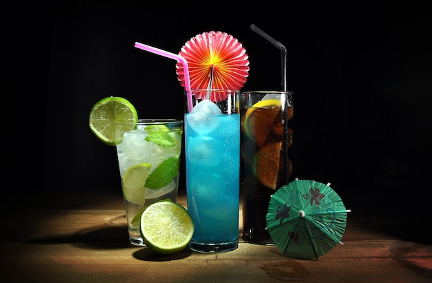 Tres cócteles diferentes y refrescantes en mesa de madera.