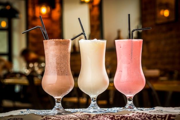 Tres cócteles en vasos de plástico con pajitas
