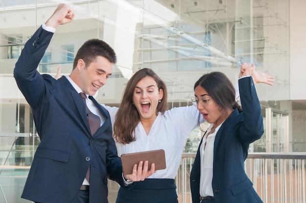 Tres colegas exultantes, recibiendo buenas noticias, levantando manos.