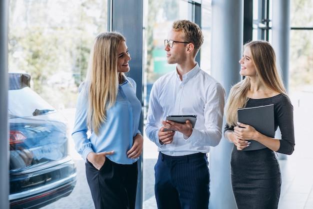 Tres colegas que trabajan en una sala de exposición de automóviles