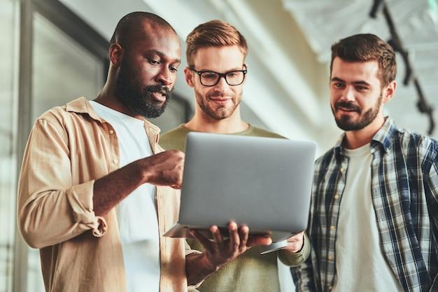 Tres colegas varones multirraciales mirando la pantalla del portátil