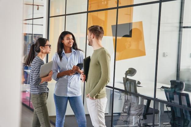 Tres compañeros de trabajo conversando en un pasillo