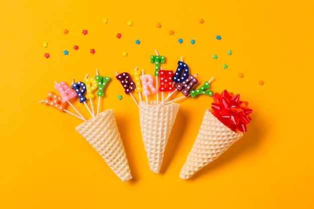Tres conos de gofres en el arco de la cinta; feliz cumpleaños texto velas con sprinkles sobre fondo amarillo