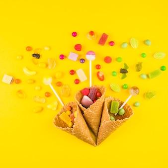 Tres conos de gofres de helado con variedades de dulces sobre fondo amarillo