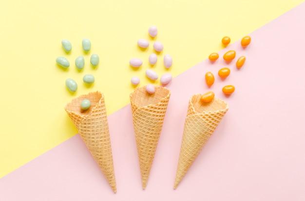 Tres conos de gofres vacíos con caramelos
