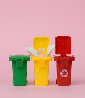 Tres contenedores de plástico multicolores sobre un fondo rosa, el concepto de clasificación correcta de la basura para su posterior reciclaje