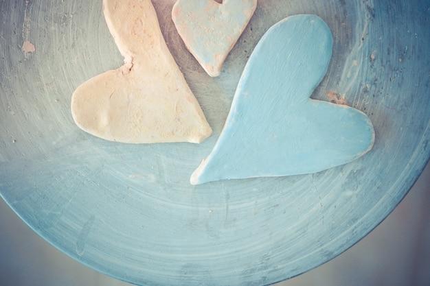 Tres corazones de arcilla pintados con pinturas en la vista superior de un torno de alfarero.