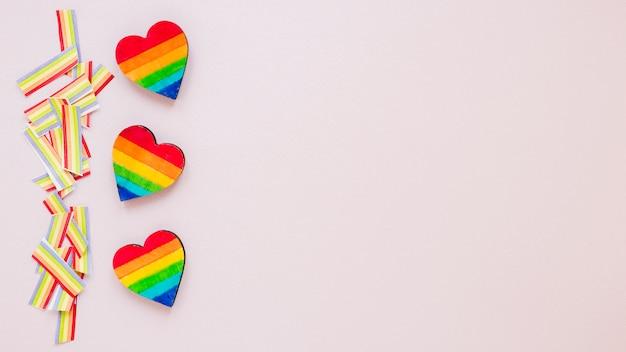 Tres corazones de arcoiris con arco iris de papel en mesa
