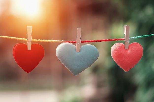 Tres corazones colgando de una cuerda. concepto de día de san valentín