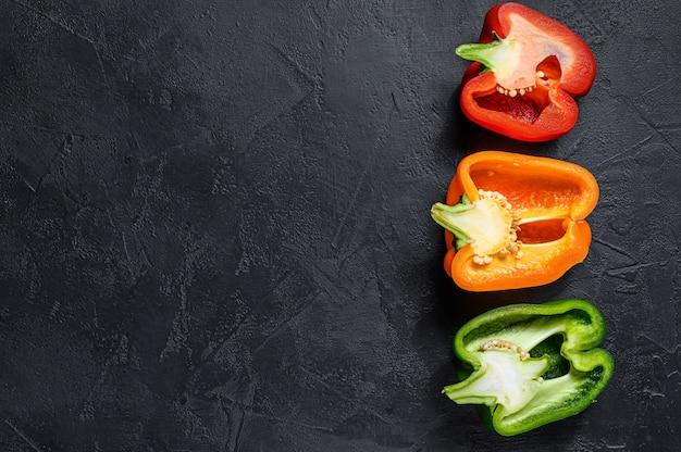 Tres cortaron pimientos naranjas, verdes y rojos.