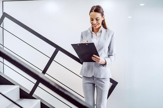 Tres cuartos de longitud de la atractiva secretaria caucásica exitosa de pie junto a la escalera y escribir tareas en el portapapeles.
