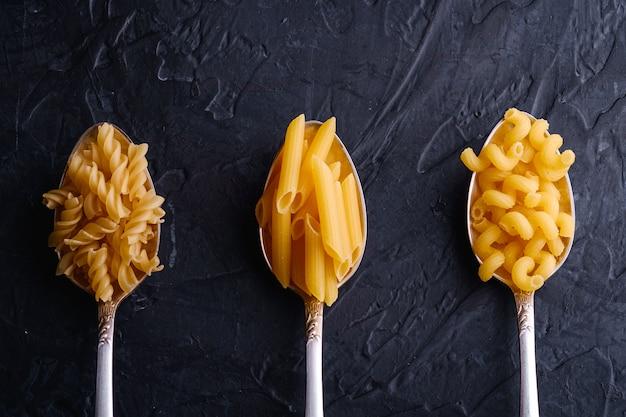 Tres cucharas de cubiertos con variedad de pasta cruda