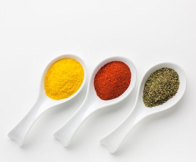 Tres cucharas con especias en polvo alineadas