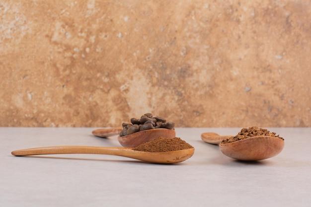 Tres cucharas de madera llenas de granos de café y cacao en polvo. foto de alta calidad