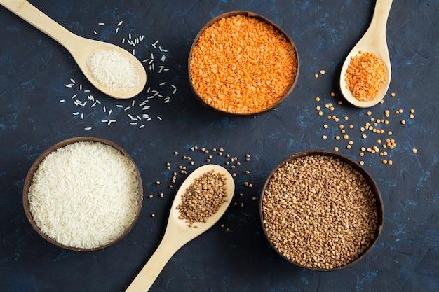 Tres cuencos llenos de cereales, lentejas, arroz y trigo sarraceno sobre un fondo azul oscuro. las cucharas de madera están llenas de granos. composición laica plana. cerrar imagen.