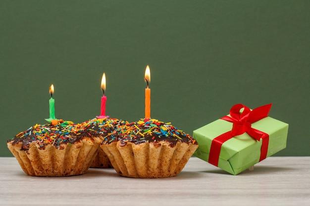 Tres deliciosos cupcakes de cumpleaños con glaseado de chocolate y caramelo, decorados con velas festivas encendidas y caja de regalo sobre fondo verde. concepto de feliz cumpleaños.